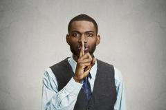 hombre-secreto-finger-en-gesto-de-los-labios-48013357